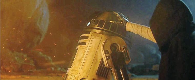 Luke Skywalker in a past memory, reaching up to R2-D2